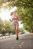 Слушать счастливой молодой женщины пригонки худенькой jogging к музыке Стоковые Фото