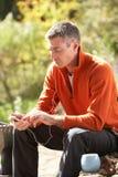 слушая игрок mp3 человека outdoors к Стоковое Изображение RF