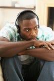 слушая софа нот человека ослабляя сидя к Стоковое Изображение
