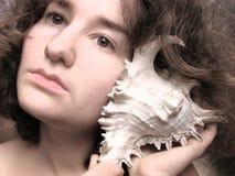 слушая seashell к женщине Стоковая Фотография