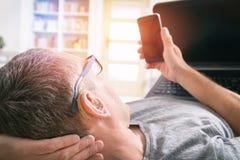 Слышать - поврежденный человек работая с компьтер-книжкой и мобильным телефоном Стоковая Фотография RF