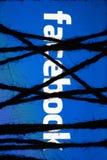 Смартфон в темноте, плотно в оболочке и связанной с грубой кабалой веревочки джута лежит с накаляя голубым экраном с текстом face стоковая фотография