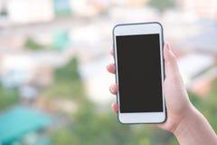 Смартфон или мобильный телефон удерживания руки с предпосылкой здания города и космосом экземпляра стоковая фотография
