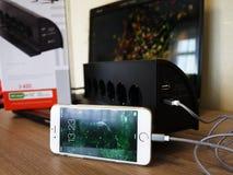 Смартфон поручает, подключен с выходом и приобретать емкость батареи стоковая фотография