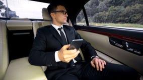 Смартфон удерживания бизнесмена в автомобиле, смотрящ окно, подготавливая для встречи стоковое изображение rf