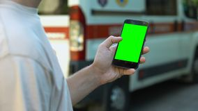 Смартфон удерживания человека, машина скорой помощи на предпосылке, онлайн медицинской консультации видеоматериал