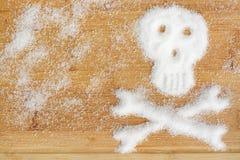 Смертельная наркомания сахара предложенная разлитыми кристаллами белого сахара формируя череп на деревянном столе Стоковые Фото