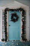 Смертная казнь через повешение венка зимы на двери дома украшенной ветвью сосны рождества с красными безделушками и декоративным  стоковые фотографии rf