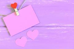 Смертная казнь через повешение зажимки для белья с розовой карточкой чистого листа бумаги 2 розовых бумажных сердца на деревянной Стоковое Изображение