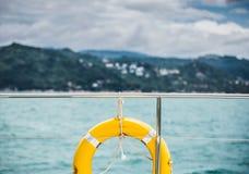Смертная казнь через повешение кольца жизни конца-вверх желтая на шлюпке с предпосылкой океана Стоковые Изображения RF