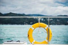 Смертная казнь через повешение кольца жизни конца-вверх желтая на шлюпке с предпосылкой океана Стоковые Изображения