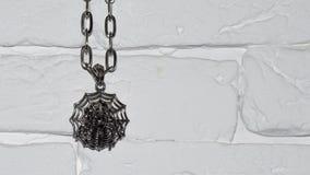 Смертная казнь через повешение паука смертной казни через повешение хеллоуина тематическая на цепи на белой каменной стене стоковое фото rf