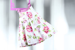 Смертная казнь через повешение платья младенца моды на вешалке на серой предпосылке Стоковая Фотография RF