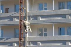 Смертная казнь через повешение работника на веревочках к красить высокого buildingdin Стоковое фото RF