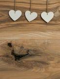 Смертная казнь через повешение сердца 3 валентинок влюбленности белизны на деревянном bac текстуры Стоковые Изображения
