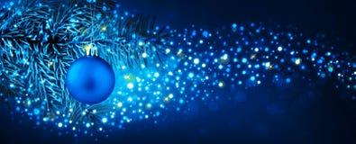 Смертная казнь через повешение шарика рождества на ветви ели с праздничной предпосылкой bokeh Стоковые Изображения