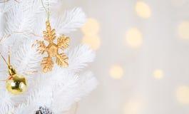 Смертная казнь через повешение шарика снежинки и оформления золота на белых wi рождественской елки Стоковые Фотографии RF