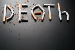 СМЕРТЬ надписи от сигарет на черной предпосылке Остановите курить Концепция куря убийств Надпись мотивации к стоковое изображение rf