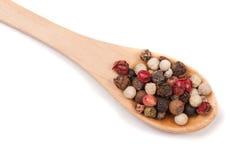 Смесь перца перцев горячих, красных, черных, белых и зеленых в деревянной ложке изолированной на белой предпосылке Взгляд сверху Стоковое Изображение RF
