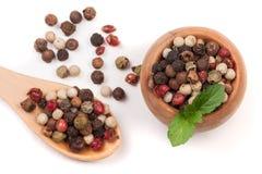 Смесь перца перцев горячих, красных, черных, белых и зеленых в деревянных шаре и ложке изолированных на белой предпосылке Стоковая Фотография