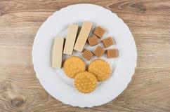 Сметанообразная тянучка, вафли, печенья в белой плите на таблице Стоковые Фото