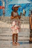 смех девушки распыляя детенышей воды зонтика Стоковое Изображение RF