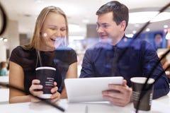 Смех женщины как человек показывает таблетку Стоковая Фотография RF