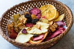 Смешанные высушенные куски плодоовощей апельсина, клубники, ананаса, вишни и Яблока с порошком циннамона в деревянной корзине Стоковые Изображения