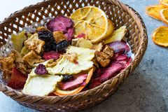 Смешанные высушенные куски плодоовощей апельсина, клубники, ананаса, вишни и Яблока с порошком циннамона в деревянной корзине Стоковое Изображение