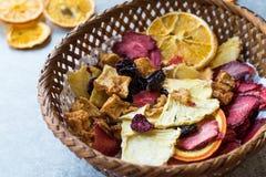 Смешанные высушенные куски плодоовощей апельсина, клубники, ананаса, вишни и Яблока с порошком циннамона в деревянной корзине Стоковая Фотография RF
