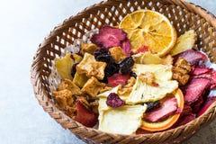 Смешанные высушенные куски плодоовощей апельсина, клубники, ананаса, вишни и Яблока с порошком циннамона в деревянной корзине Стоковое Изображение RF
