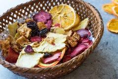 Смешанные высушенные куски плодоовощей апельсина, клубники, ананаса, вишни и Яблока с порошком циннамона в деревянной корзине Стоковые Изображения RF
