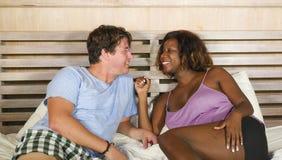Смешанные пары этничности в любов прижимаясь совместно дома в кровати с красивыми шаловливыми черными Афро-американскими женщиной стоковое изображение