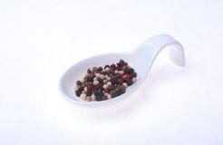 Смешанные corns черного, белого и красного перца в шаре изолированном на белой предпосылке Стоковые Фото