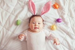 Смешанный азиатский младенец нося розовые уши зайчика пасхи лежа на кровати в спальне с красочными яйцами стоковое фото rf