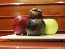 Смешанный мангустан сливы яблок плодоовощей на плите против деревянной предпосылки стоковые фото