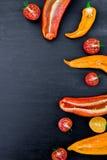Смешанный наполовину красного и желтого перца с зеленой ветвью около томата вишни на черном backround Взгляд сверху Рамка скопиру Стоковая Фотография RF