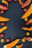 Смешанный наполовину красного и желтого перца с зеленой ветвью около томата вишни на черном backround Взгляд сверху Рамка скопиру Стоковые Изображения RF