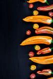 Смешанный наполовину красного и желтого перца с зеленой ветвью около томата вишни на черной предпосылке Взгляд сверху Рамка скопи Стоковая Фотография RF