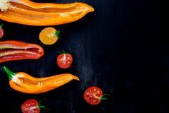 Смешанный наполовину красного и желтого перца с зеленой ветвью около томата вишни на черном backround Взгляд сверху Рамка скопиру Стоковое Фото