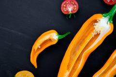 Смешанный наполовину красного и желтого перца с зеленой ветвью около томата вишни на черной предпосылке Взгляд сверху скопируйте  Стоковое Фото
