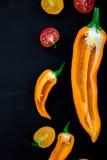 Смешанный наполовину красного и желтого перца с зеленой ветвью около томата вишни на черной предпосылке Взгляд сверху скопируйте  Стоковые Фото