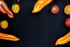 Смешанный наполовину красного и желтого перца с зеленой ветвью около томата вишни на черной предпосылке Взгляд сверху Рамка скопи Стоковое фото RF