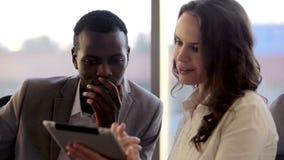 2 смешанных коллеги работая с таблеткой Они обсуждая идеи дела сидя в современном светлом офисе акции видеоматериалы