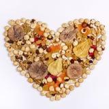 Смешивание гаек и высушенные плодоовощи в форме сердца на белом квадрате взгляд сверху предпосылки стоковые фото