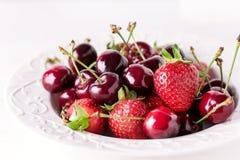 Смешивание клубник и вишни в поднимающем вверх клубники и вишни белой плиты красивое зрелое сочное близкое Стоковое фото RF
