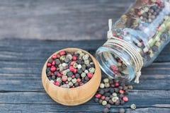 Смешивание перчинки в деревянном шаре и стекло раздражают на старом темном деревянном столе Стоковое Изображение