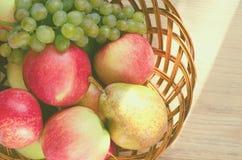 Смешивание плодоовощей в деревянной корзине, освещенное лучем солнца стоковая фотография
