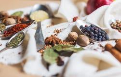 Смешивание различных специй и трав, кашевар и ингридиенты кухни на таблице с оформлением лист и плодоовощ залива Стоковое Изображение