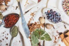 Смешивание различных специй и трав, кашевар и ингридиенты кухни на таблице с оформлением лист и плодоовощ залива Стоковые Фотографии RF